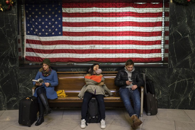 Passengers wait after their flights were delayed at LaGuardia Airport's Terminal A during a winter storm in New York January 3, 2014. A major snowstorm producing blizzard-like conditions hammered the northeastern United States on Friday, causing 2,000 U.S. flight delays and cancellations, paralyzing road travel, and closing schools and government offices. (REUTERS/Zoran Milich)