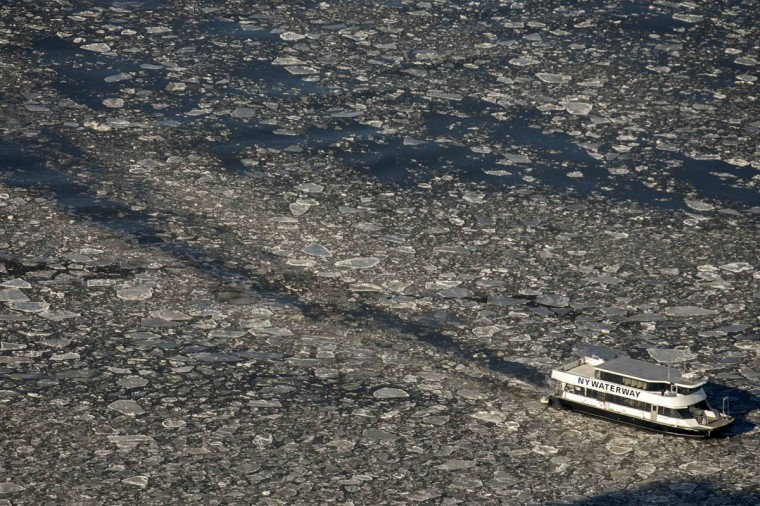 A commuter ferry navigates through the ice flow in the Hudson River between New Jersey and lower Manhattan in New York January 9, 2014. (REUTERS/Brendan McDermid)