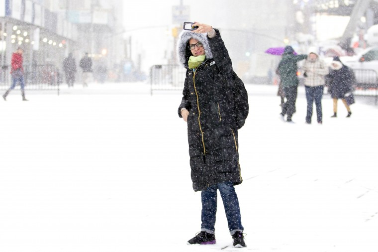 A woman takes a photo during a snowstorm in Times Square in New York January 21, 2014. A fast-moving cold front will plunge the U.S. Midwest into a deep freeze on Tuesday and dump up to a foot (30 cm) of snow on parts of the East Coast, forecasters said. (REUTERS/Brendan McDermid)