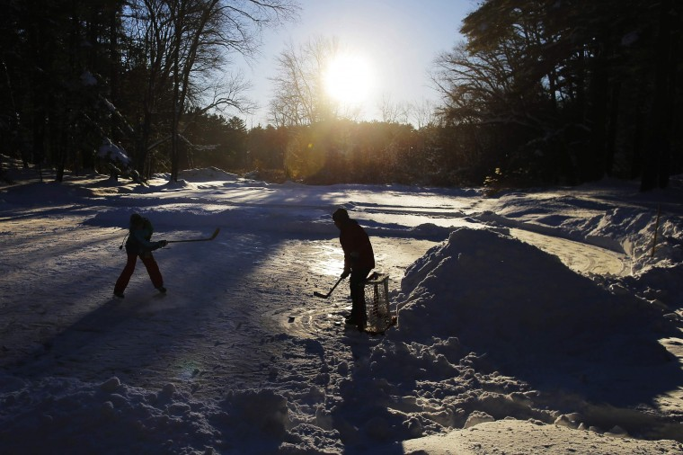Kids play hockey on a pond following a winter nor'easter snow storm in Boxford, Massachusetts January 3, 2014. The heaviest snowfall came north of Boston, where the towns of Boxford and Topsfield, about 24 miles away, each saw close to two feet of accumulation as a heavy snowstorm and dangerously cold conditions gripped the northeastern United States. (REUTERS/Brian Snyder)