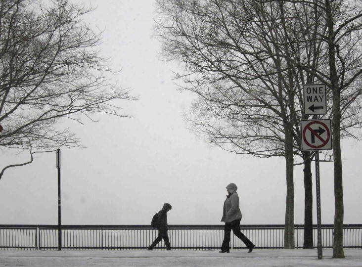 People walk in a park along the Hudson River across from New York as snow begins to fall in Hoboken, New Jersey January 21, 2014. A fast-moving cold front will plunge the U.S. Midwest into a deep freeze on Tuesday and dump up to a foot (30 cm) of snow on parts of the East Coast, forecasters said. (REUTERS/Gary Hershorn)