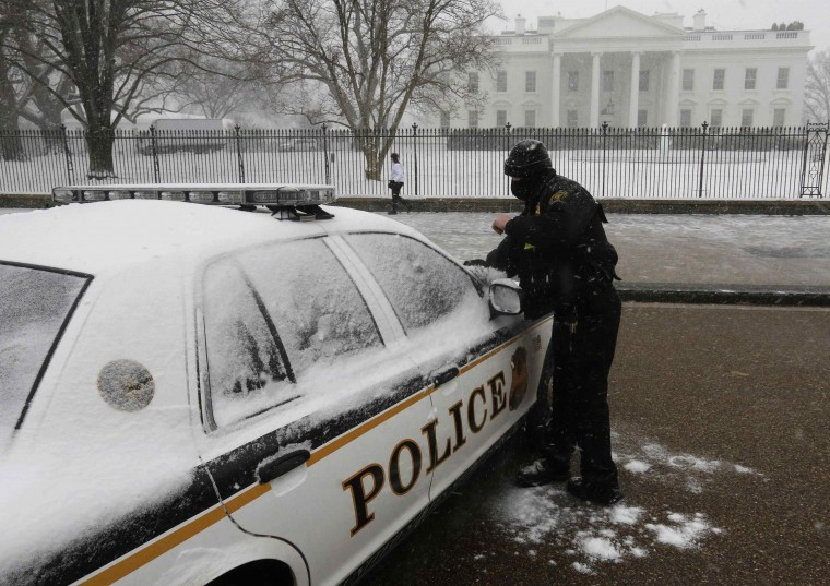 A member of the U.S. Secret Service Uniformed Division brushes snow off his vehicle in front of the White House in Washington during a snowstorm January 21, 2014. (REUTERS/Larry Downing)