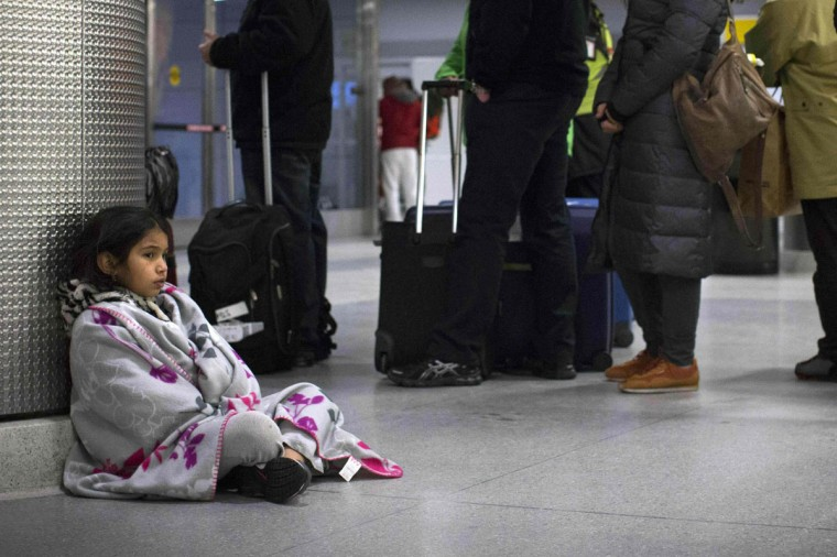 A child tries to keep warm while sitting next to a service line at the John F. Kennedy International Airport in New York January 21, 2014. A winter storm packing snow and Arctic cold slammed the northeastern United States on Tuesday, grounding 3,000 flights, shutting down governments and schools and making travel a potential nightmare for millions. (REUTERS/Andrew Kelly)