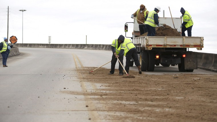 Workers with the city of Mobile shovel dirt on a bridge as cold weather descends on Mobile, Ala. (REUTERS/Lyle Ratliff)