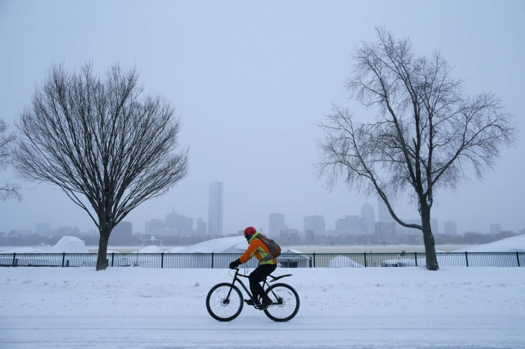 A cyclist rides along snow covered Memorial Drive during a winter nor'easter snow storm in Cambridge, Massachusetts on January 3, 2014. (REUTERS/Brian Snyder)