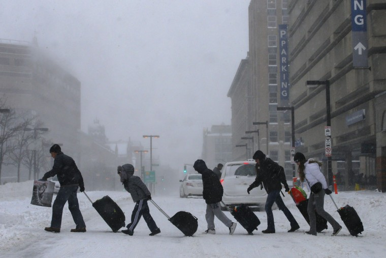 Travelers leave the Back Bay train and subway station during a winter nor'easter snow storm in Boston, Massachusetts January 3, 2014. A major snowstorm producing blizzard-like conditions brought bone-chilling temperatures and high winds from the lower Mississippi Valley to the Atlantic coast, with nearly 2 feet (60 cm) of snow falling in some areas of Massachusetts. (REUTERS/Brian Snyder)