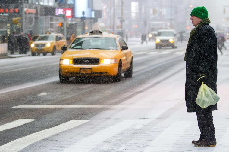 A man crosses a street in Times Square, New York January 21, 2014. A fast-moving cold front will plunge the U.S. Midwest into a deep freeze on Tuesday and dump up to a foot (30 cm) of snow on parts of the East Coast, forecasters said. (REUTERS/Brendan McDermid)