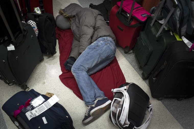 A man sleeps amongst baggage at the John F. Kennedy International Airport in New York January 21, 2014. A winter storm packing snow and Arctic cold slammed the northeastern United States on Tuesday, grounding 3,000 flights, shutting down governments and schools and making travel a potential nightmare for millions. (REUTERS/Andrew Kelly)