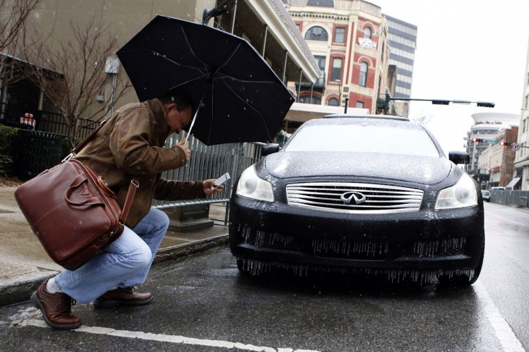 Tomay Ozgokmen, a professor from the University of Miami, takes a picture of an iced-over car as cold weather descends on Mobile, Ala. (REUTERS/Lyle Ratliff)
