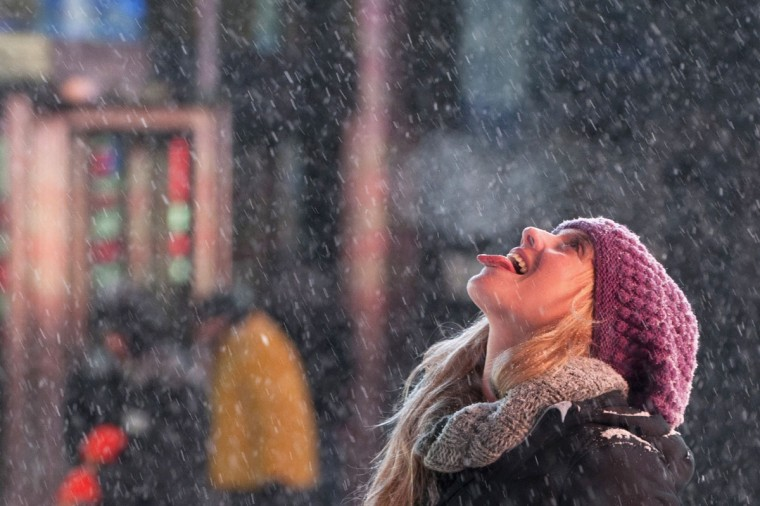 A tourist catches snowflakes on her tongue during snow fall in Times Square, Midtown, New York January 2, 2014. A major snowstorm producing blizzard-like conditions hammered the northeastern United States on Friday, causing more than 1,000 U.S. flight delays and cancellations, paralyzing road travel, and closing schools and government offices. (REUTERS/Darren Ornitz)