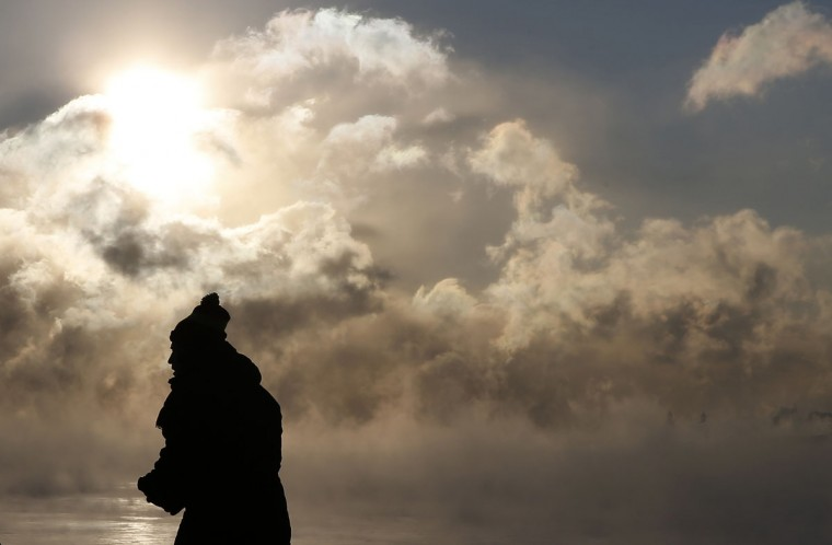 A man is silhouetted against the sun and arctic sea smoke rising off Lake Michigan in Chicago. (REUTERS/Jim Young)