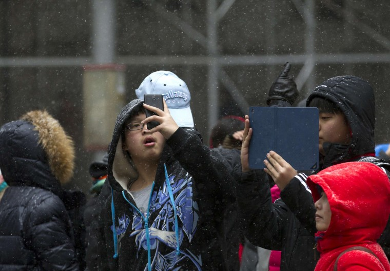 School children take photos during a snow storm in Manhattan's financial district in New York January 21, 2014. A fast-moving cold front will plunge the U.S. Midwest into a deep freeze on Tuesday and dump up to a foot (30 cm) of snow on parts of the East Coast, forecasters said. (REUTERS/Brendan McDermid)