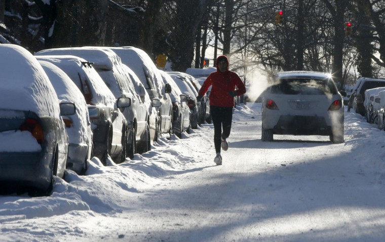 A man runs down a street past snow covered cars in the Park Slope section of Brooklyn in New York City, January 22, 2014. The northeastern United States on Wednesday dug out from a storm that dumped over a foot of snow in many places with frigid, windy weather keeping some schools and offices closed and flights canceled. (REUTERS/Mike Segar)