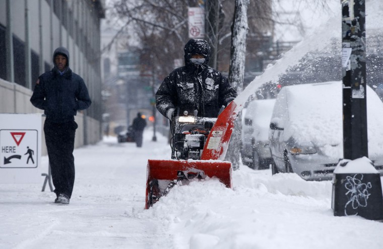 A man clears snow with a snow blower in the South Bronx section of New York City on January 3, 2014. (REUTERS/Mike Segar)