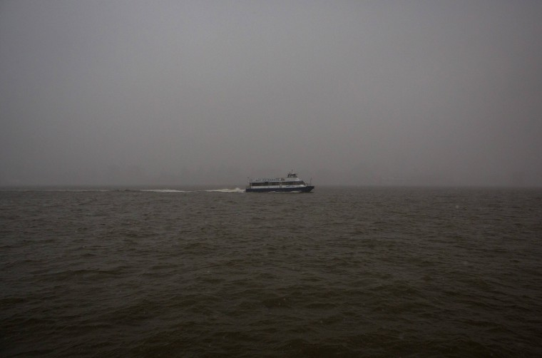 A ferry is seen on the Hudson River with the New York skyline obscured by fog from Hoboken, New Jersey January 21, 2014. A fast-moving cold front will plunge the U.S. Midwest into a deep freeze on Tuesday and dump up to a foot (30 cm) of snow on parts of the East Coast, forecasters said. (REUTERS/Eric Thayer)