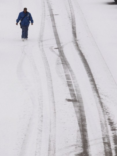 A man walks through a snow-covered parking lot after a rare snowstorm in Adairsville, Ga. (REUTERS/Tami Chappell)