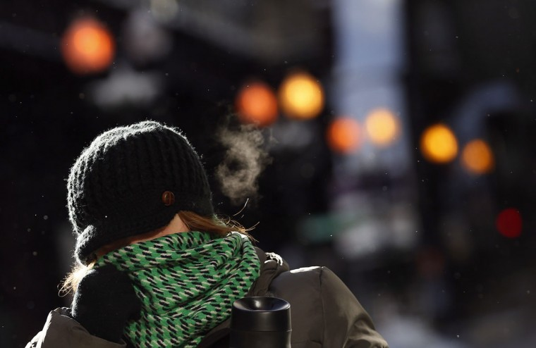 A woman covers her face to protect herself from the frigid cold temperatures though downtown Chicago. (REUTERS/Jim Young)