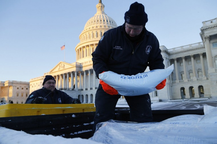 Workers load ice-melting compound into a spreader at the U.S. Capitol in Washington January 22, 2014. The northeastern United States on Wednesday dug out from a storm that dumped over a foot of snow in many places with frigid, windy weather keeping some schools and offices closed and flights canceled. (REUTERS/Jonathan Ernst)