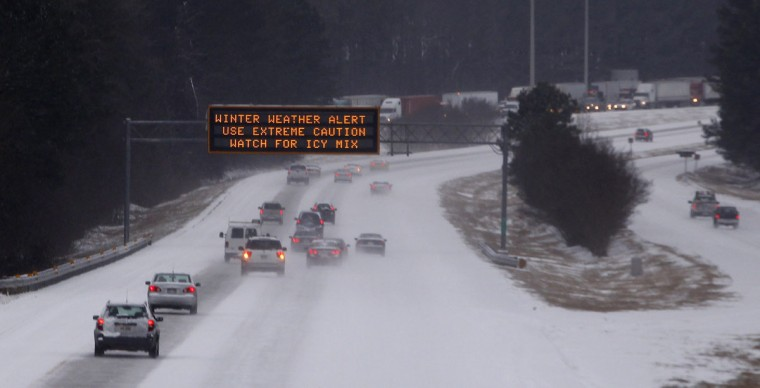 Cars drive under a traffic sign displaying winter storm warnings after a rare snowstorm in Kennesaw, Ga. (REUTERS/Tami Chappell)