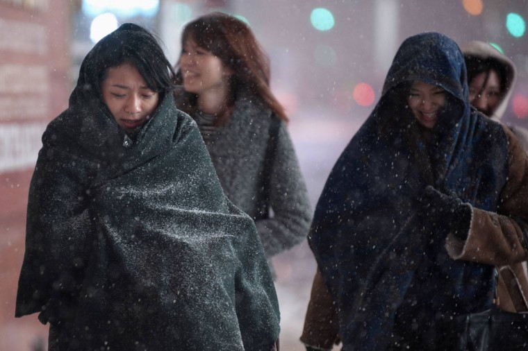 Women cover themselves from the snow while making their way through Times Square, Midtown, New York on January 3, 2014. (REUTERS/Darren Ornitz)