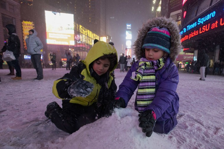 Children play with snow on the streets of Times Square, Midtown, New York on January 2, 2014. (REUTERS/Darren Ornitz)