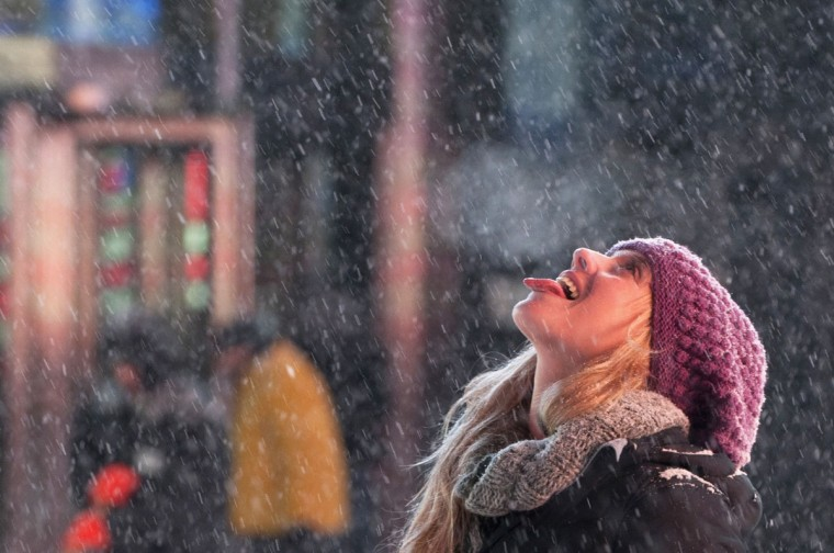 A tourist catches snowflakes on her tongue during snow fall in Times Square, Midtown, New York on January 2, 2014. (REUTERS/Darren Ornitz )