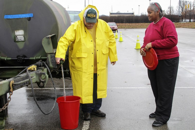Melvina Lang (R) of Dunbar, West Virginia gets a bucket filled with water at the South Charleston water filling station in Charleston, West Virginia, January 11, 2014. Up to 300,000 West Virginia residents were told not to drink tap water January 10, 2014 after a chemical spill called its safety into question, and health officials said water in the affected area should only be used for flushing toilets and fighting fires. (REUTERS/Lisa Hechesky)