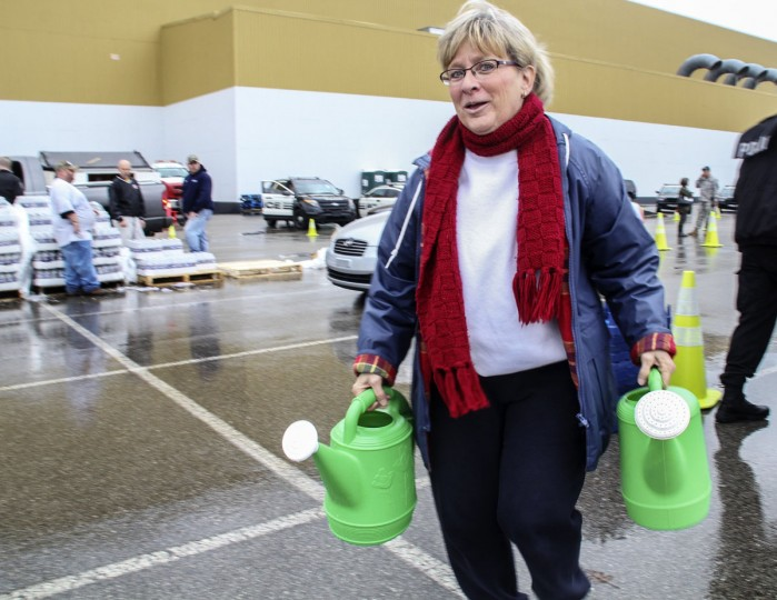 Cathy Mabe of Spring Hill, West Virginia makes use of a couple of watering cans to carry water at a bring-your-own-containers water filling station in South Charleston, West Virginia, January 11, 2014. Up to 300,000 West Virginia residents were told not to drink tap water January 10, 2014 after a chemical spill called its safety into question, and health officials said water in the affected area should only be used for flushing toilets and fighting fires. (REUTERS/Lisa Hechesky)