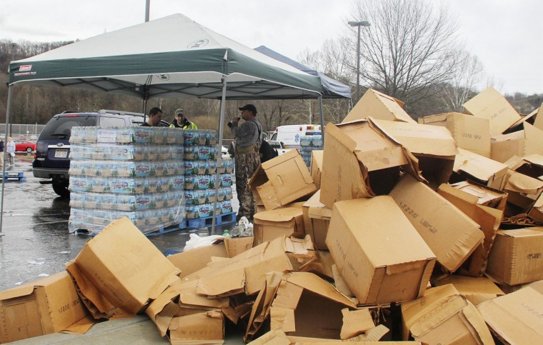 Cardboard boxes are discarded as the Poca Volunteer Fire Department distributes bottled water at Poca High School in Poca, West Virginia, January 11, 2014. Up to 300,000 West Virginia residents were told not to drink tap water January 10, 2014 after a chemical spill called its safety into question, and health officials said water in the affected area should only be used for flushing toilets and fighting fires. (REUTERS/Lisa Hechesky)