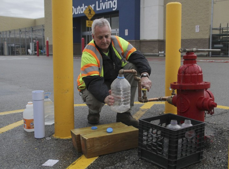 A city worker distributes water at a local store in Charleston, West Virginia January 10, 2014. Up to 300,000 West Virginia residents were told not to drink tap water on Friday after a chemical spill called its safety into question, and health officials said water in the affected area should only be used for flushing toilets and fighting fires. (REUTERS/Lisa Hechesky)