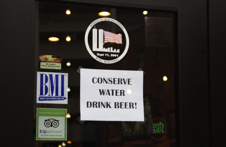 A sign is posted on Adelphia Sports Bar and Grille is pictured in downtown Charleston, West Virginia, January 13, 2014. West Virginia officials on Monday lifted a ban on drinking or bathing with tap water in some areas of the state hit by a chemical spill that affected hundreds of thousands of people for five days, Governor Earl Ray Tomblin said. (REUTERS/Lisa Hechesky)