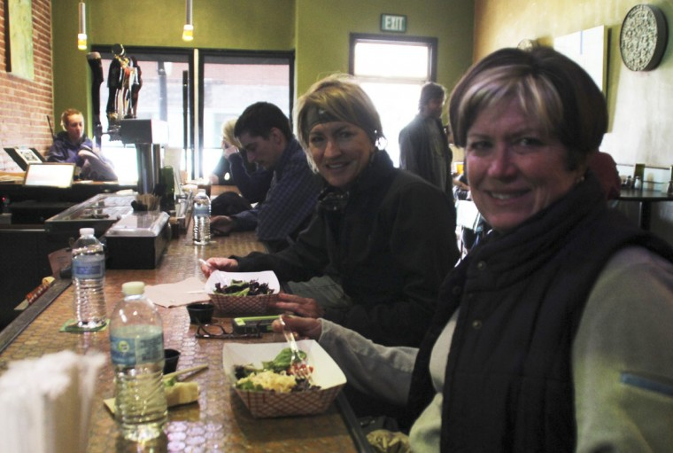 Jenette Wheatcraft (R) and Sandy Kee (2nd R) are served with paper trays and bottled water in Bluegrass Kitchen, one of the few conditionally reopened restaurants in Charleston, West Virginia January 13, 2014. West Virginia officials on Monday lifted a ban on drinking or bathing with tap water in some areas of the state hit by a chemical spill that affected hundreds of thousands of people for five days, Governor Earl Ray Tomblin said. (REUTERS/Lisa Hechesky)
