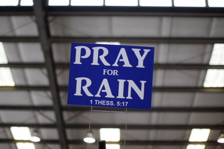 A sign advising to pray for rain hangs above an exhibit area at the 47th Annual World Ag Expo in Tulare, California, February 12, 2014. The expo takes place as a third year of drought plagues California farmers with the driest year on record and prompting California Governor Jerry Brown to declare a statewide drought emergency. (David McNew/ Reuters photo)