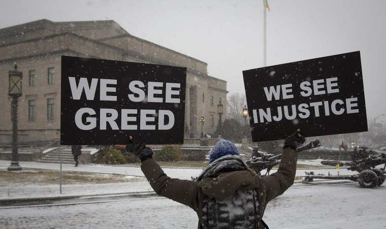 A woman holds up signs as she stands in quiet protest outside the War Memorial building in Trenton, New Jersey January 21, 2014. Governor Chris Christie is being sworn in today for his second term. (REUTERS/Carlo Allegri)