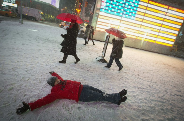 A man makes a snow angel in the middle of Times Square in New York on January 3, 2014. (REUTERS/Carlo Allegri)