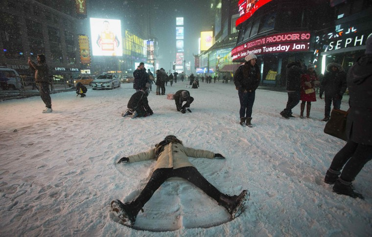 A woman makes a snow angel in the middle of Times Square in New York on January 3, 2014. (REUTERS/Carlo Allegri)