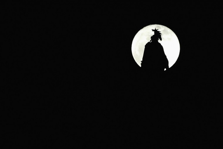 A full moon rises over the Statue of Freedom atop the dome of the U.S. Capitol in Washington, January 16, 2014. REUTERS/Jonathan Ernst