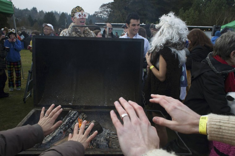 Participants warm up around a fire after entering Lake Washington during the 12th annual Polar Bear Plunge in Seattle on January 1, 2014. Hundreds participated in the chilly New Year's Day tradition, organized by Seattle Parks and Recreation and held at Matthews Beach. (REUTERS/David Ryder)
