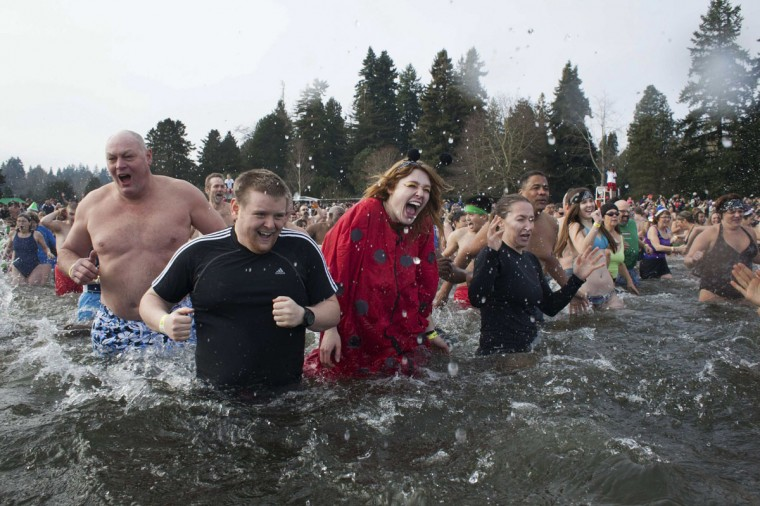Participants react after entering Lake Washington during the 12th annual Polar Bear Plunge in Seattle on January 1, 2014. Hundreds participated in the chilly New Year's Day tradition, organized by Seattle Parks and Recreation and held at Matthews Beach. (REUTERS/David Ryder)