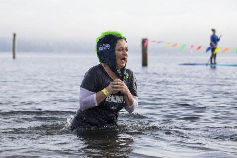 A woman reacts after entering Lake Washington during the 12th annual Polar Bear Plunge in Seattle on January 1, 2014. Hundreds participated in the chilly New Year's Day tradition, organized by Seattle Parks and Recreation and held at Matthews Beach. (REUTERS/David Ryder)