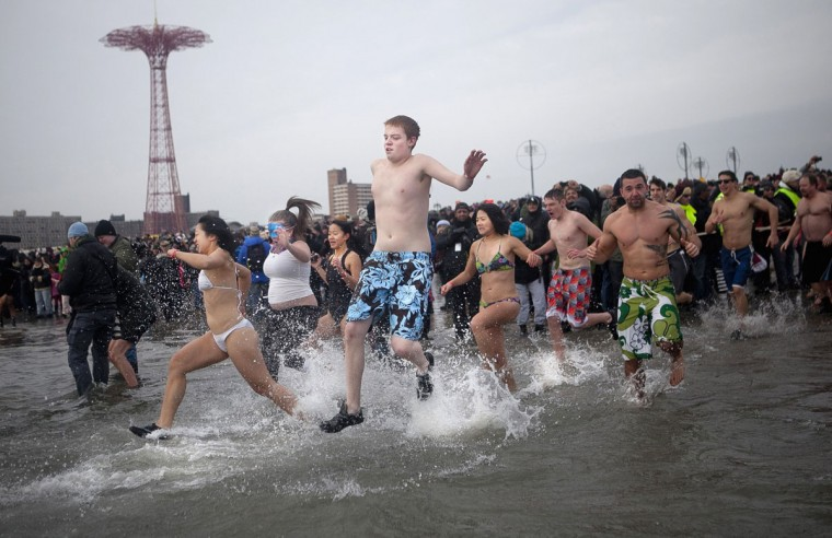 People participate in the annual Coney Island Polar Bear Club dip, in the Brooklyn borough of New York on January 1, 2014. The Coney Island Polar Bear Club is the oldest winter bathing organization in the U.S. and every New Year's Day holds the winter plunge, which attracts thousands of participants. (REUTERS/Allison Joyce)
