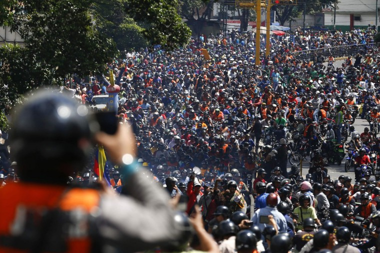 Thousands of motorcyclists drive during a protest against possible regulation and schedule bans as a measure to combat insecurity in Caracas January 31, 2014. Nearly 2,000 motorcyclists protested in Caracas on Friday, hooting their horns and waving Venezuelan flags outside a government office as they condemned a night ban that authorities imposed in a bid to curb crime. Officials in Caracas and other areas made it illegal to ride a motorcycle after 9pm. (REUTERS/Jorge Silva)