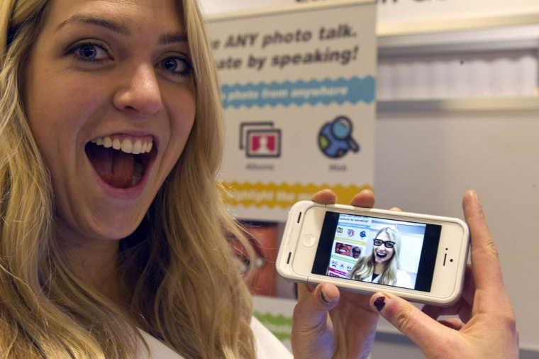 Gillian Pennington holds a smartphone with an animated, speaking image of herself in the Freak 'n Genius booth during the 2014 International Consumer Electronics Show (CES) in Las Vegas, Nevada. Using the YAKiT app, a free download for iOS, a user can easily add talking animation to any photo. (Steve Marcus/Reuters photo)