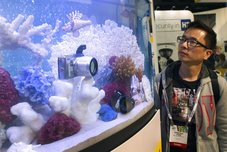 Sampson Yang looks at a waterproof Nikon 1 Aw1 at the Nikon booth during the 2014 International Consumer Electronics Show (CES) in Las Vegas, Nevada. The camera retails for $800 and is available in stores. (Steve Marcus/Reuters photo)