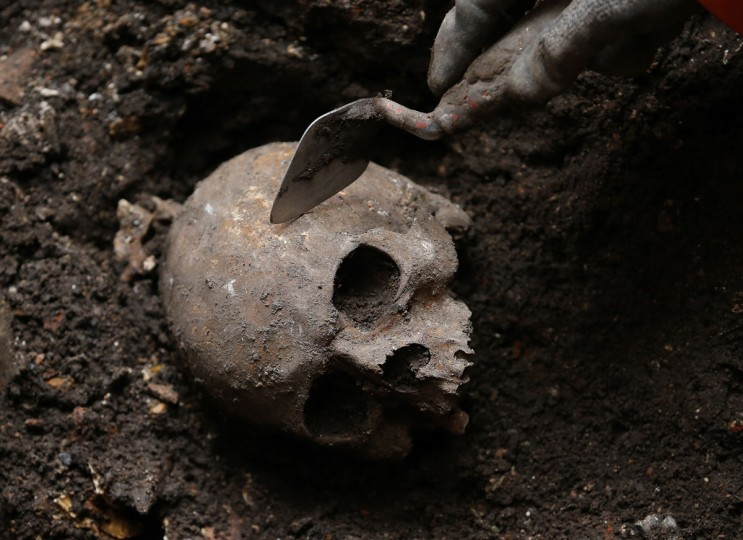 An archaeologist digs out a skull from the site of the graveyard of the Bethlehem, or Bedlam, hospital next to Liverpool Street Station in the City of London on August 7, 2013. (REUTERS/Andrew Winning)
