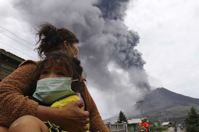 A mother holds her child as Mount Sinabung spews ash and hot lava during an eruption in Perteguhan village in the Karo district of Indonesia's north Sumatra province on September 17, 2013. Mount Sinabung threw more volcanic ash into air, covering the surrounding areas as authorities prepared more temporary shelters for evacuees. (REUTERS/Roni Bintang)