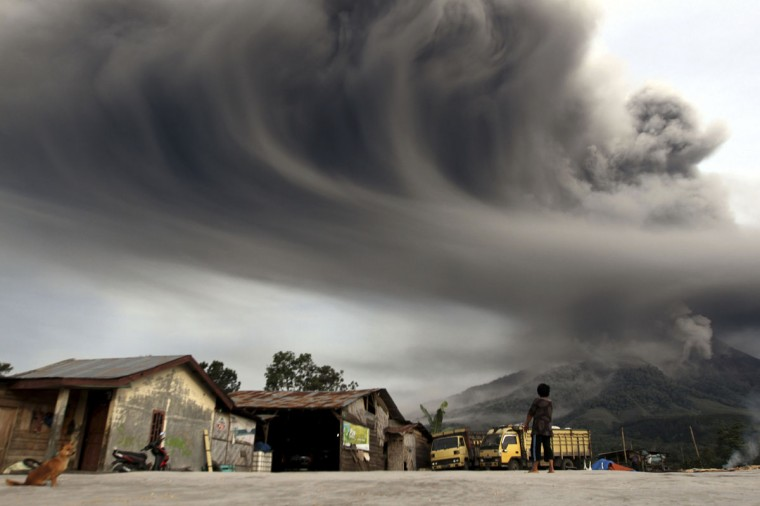 A woman looks on as Mount Sinabung spews ash, as pictured from Sibintun village in Karo district, Indonesia's north Sumatra province on November 18, 2013. Mount Sinabung continued to spew volcanic ash, throwing a plume 8,000 meters into the atmosphere as thousands of residents remained in temporary shelters fearful of more eruptions. (REUTERS/Roni Bintang)