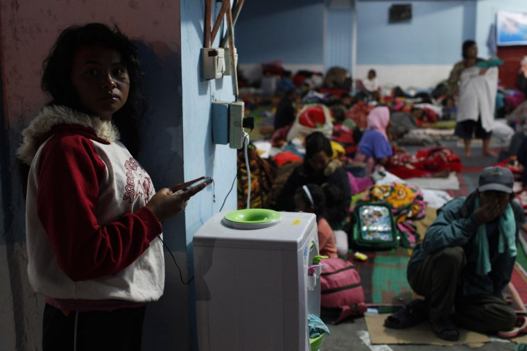 A villager charges her mobile phone at a temporary shelter for people evacuated due to increased activity by the Mount Sinabung volcano, at Kabanjahe village in Karo district, Indonesia's North Sumatra province November 25, 2013. (REUTERS/Beawiharta)