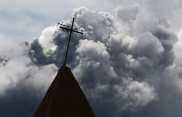 A cross is seen atop a church steeple as ash from Mount Sinabung spews in the background, as seen from Kebayaken village in Karo district, Indonesia's North Sumatra province November 30, 2013. (REUTERS/Beawiharta)