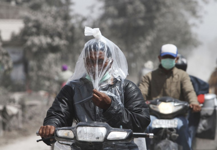 A villager riding a motorcycle covers his face with a plastic sheet to avoid ash from Mount Sinabung volcano at Tiga Pancur village in Karo district, Indonesia's North Sumatra province, early morning January 6, 2014. About 20,000 villagers have been evacuated since authorities raised the alert status for Sinabung to the highest level in November 2013. (REUTERS/Roni Bintang)